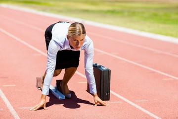 Businesswoman with briefcase ready to run
