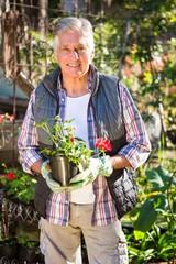 Portrait of confident gardener holding potted plant at garden