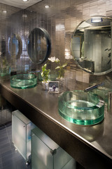 Mirrored bathroom with two glass sinks