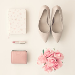 Heel shoes, notebook, lipstick, wallet and roses flat lay