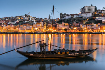Traditional Rabelo boat designed to carry wine down Douro river with city skyline behind, Porto, Portugal