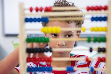 Boy playing with abacus in classroom