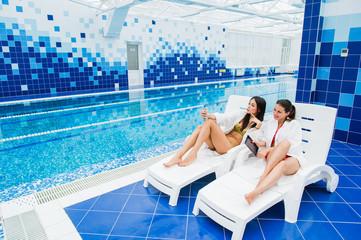 Two beautiful girls taking a selfie next to swimming pool