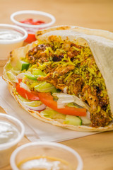 A bright photo of chicken shawarma sandwich, an Arabic food. Wrapped in pita bread along with rice, vegetables, yogurt, ketchup, and hummus.