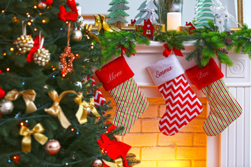 Christmas stockings hanging on fireplace near fir tree, close up view