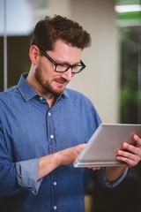 Happy businessman using digital tablet at office