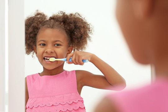 Cute African American girl brushing teeth and looking in mirror in bathroom