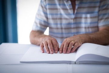 Blind man reading a braille book