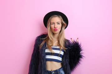 Young cool woman on pink wall background