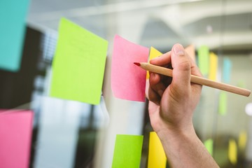 Cropped image of businessman writing on sticky notes