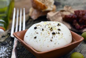 Burrata in Keramik auf Holz / Nahaufnahme / Foodstyling