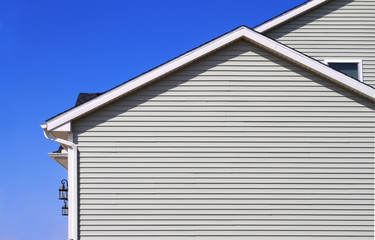 New home with gray vinyl siding and blue sky in the background