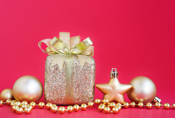 Gift box and gold christmas ornament over red background