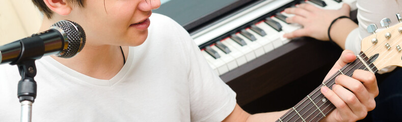 Teenage boy playing electric guitar and singing while girl plays on piano
