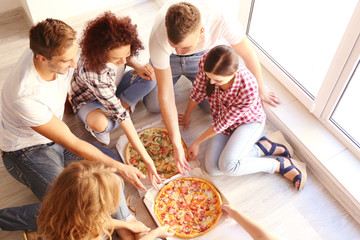 Friends having fun and eating pizza while sitting on floor