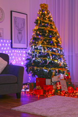 Decorated Christmas tree and boxes with presents in living room