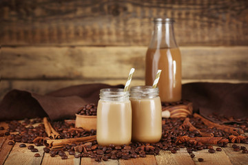 Glass jars with delicious milk dessert and coffee beans on table, closeup