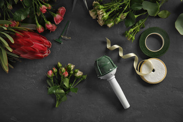 Beautiful flowers and florist equipment on dark background