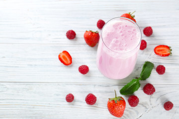 Glass of delicious milkshake and fresh berries on white wooden background