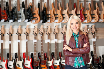 Female saleswoman with guitars in shop