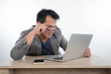 young businessman Stressful jobs using a laptop sitting thinking