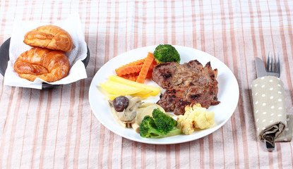 Home made ,Pork steak and mixed vegetables with croissants .