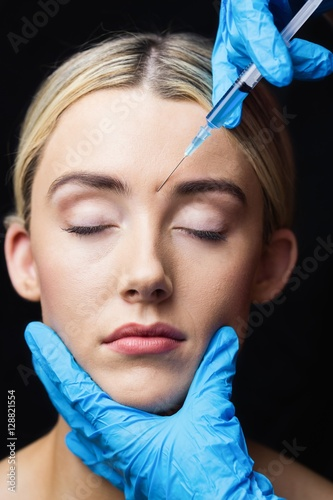 woman receiving botox injection on her forehead photo libre de droits sur la banque d 39 images. Black Bedroom Furniture Sets. Home Design Ideas
