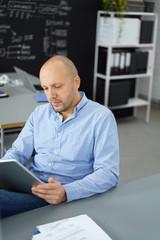 geschäftsmann liest nachrichten am tablet