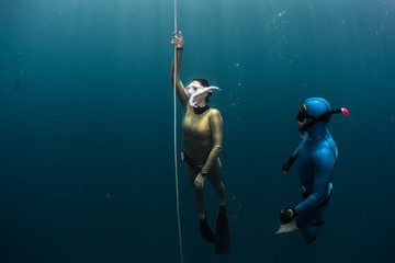 Wall Mural - Two lady free diver ascending along the rope in the depth