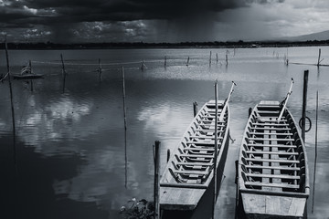 empty wooden fishing boat in raining in quiet lake sky black and white tone.
