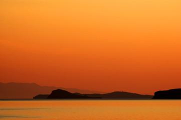 Fantastic sunrise with islands on the skyline. Baikal lake area.