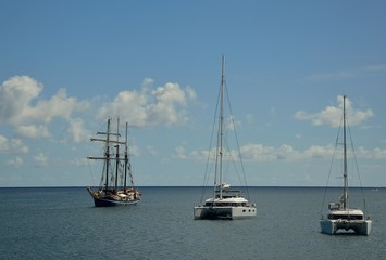 Catamarans and great sailboat anchored in the bay