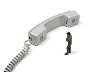 Toy Person Standing Next to Telephone Receiver