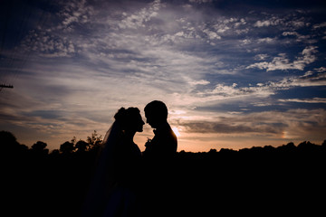 dark silhouettes of groom and bride at sunset