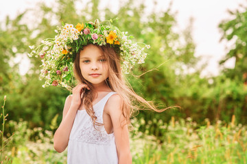Cute smiling little girl  with flower wreath on the meadow at th