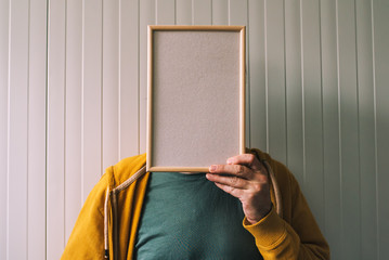 Unrecognizable man posing with blank picture frame over his face