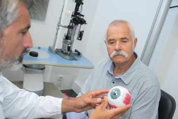 ophthalmologist shows an old patient his view problem
