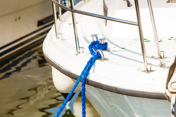 Tied blue sailing rope on white boat
