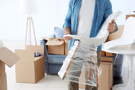 House moving concept. Man holding chair, closeup