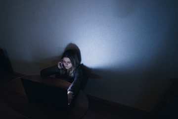 teenager girl sitting at the computer at night. It is a victim of excessive harassment and bullying stalker. she was afraid