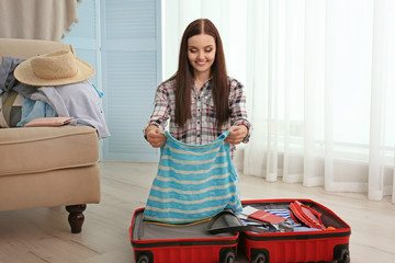 Young woman putting clothes in suitcase in room