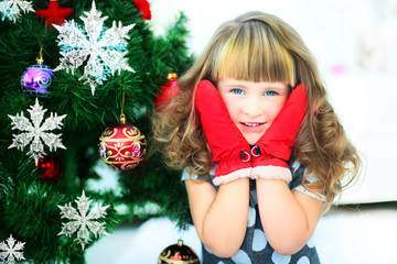 Portrait of happy girl with red mittens ball by Christmas tree