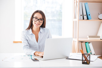 Businesswoman sitting in her office and using laptop