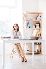 Businesswoman sitting in her office and talking by phone