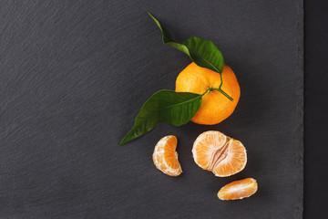 Orange mandarin on the black slate stone background