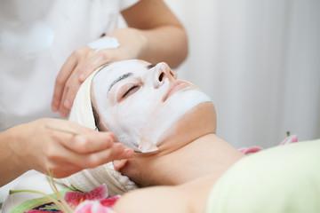 Face mask.Beautiful young girl at cosmetics getting facial treatment