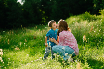 Happy mother kissing her son in summer park