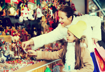 mother with small daughter staring at counter of Christmas marke