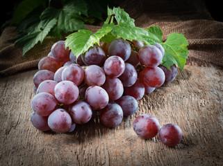 Fototapete - Dark grape bunch. Organic fruit with leaves.