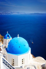 traditional blue dome of church with bellfry against blue sea, Oia, Santorini, retro toned